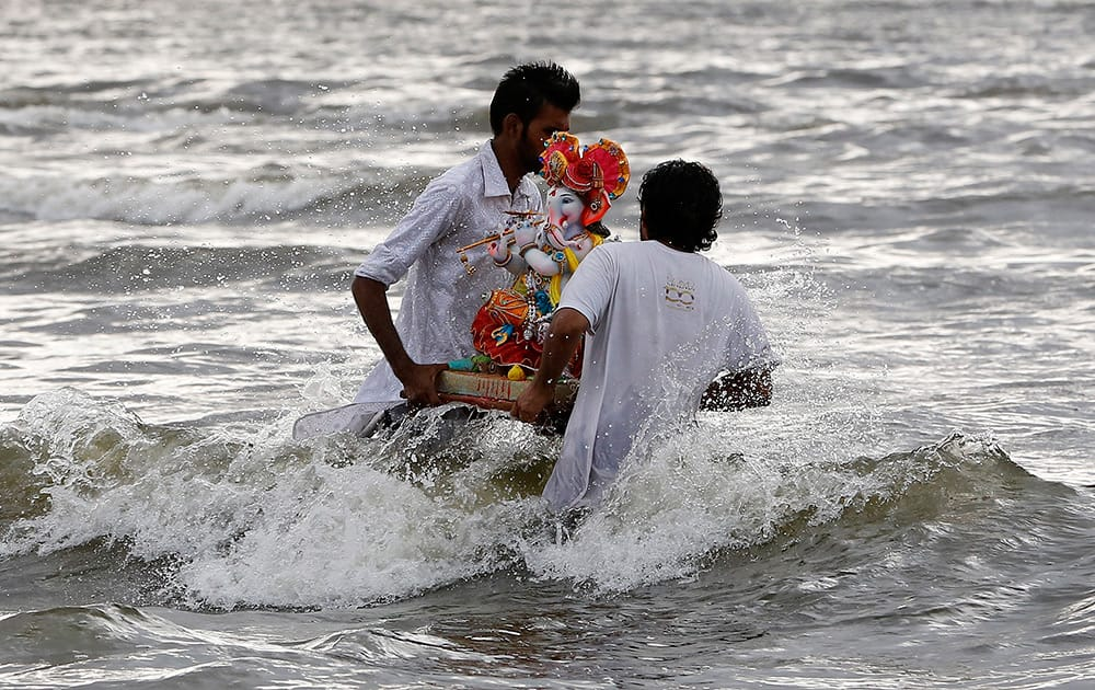 Hindu devotees carry an idol of God Ganesha for immersion in a water body on the second day of the ten-day Ganesh festival in Mumbai.