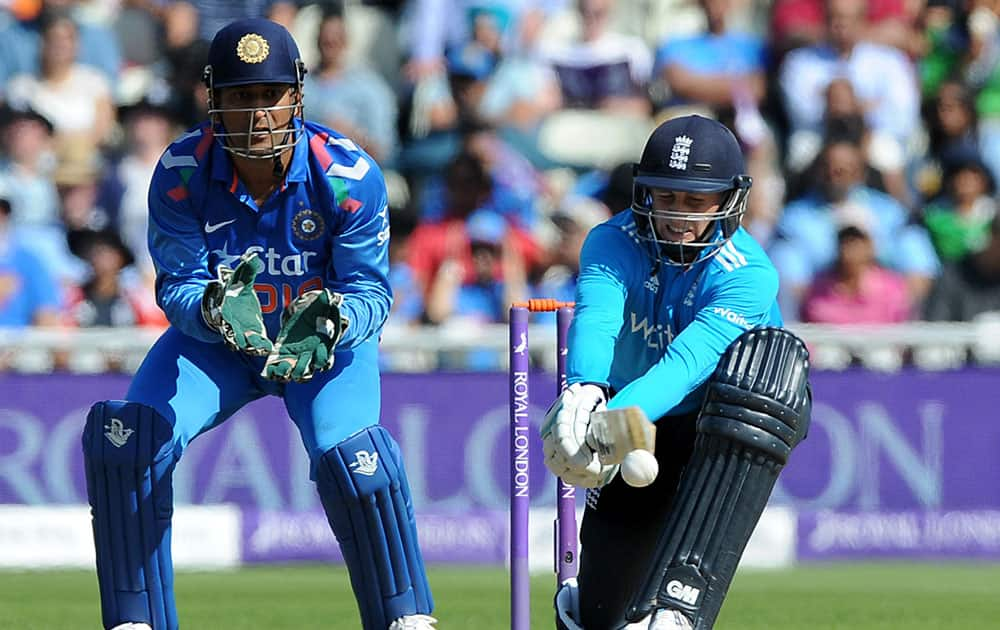 England's Joe Root strikes the ball watched by India's M.S. Dhoni, left, during the fourth One Day International match between England and India at Edgbaston cricket ground, Birmingham.