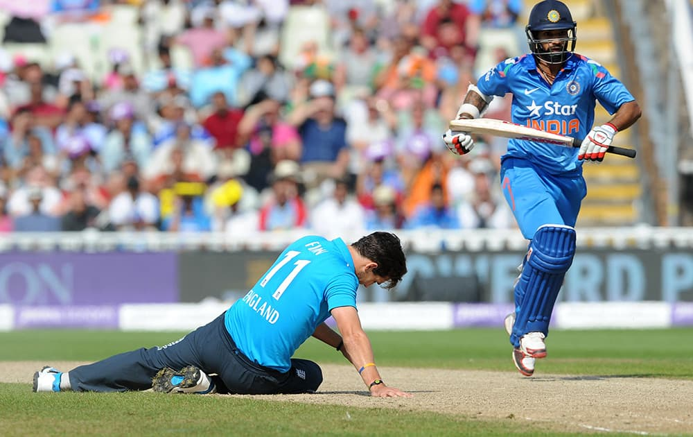England's Steven Finn on the floor as India's Shikhar Dhawan runs between wickets during the fourth One Day International match between England and India at Edgbaston cricket ground, Birmingham, England.