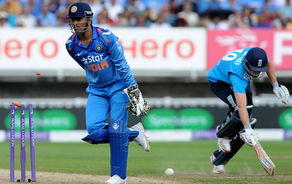 England's Chris Woakes is run out for 10 runs watched by India's wicket keeper and captain M S Dhoni during the fourth One Day International match between England and India at Edgbaston cricket ground, Birmingham, England.