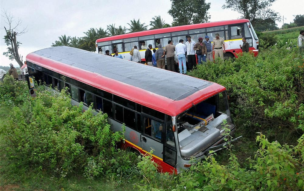 People standing near a bus that slided off the road near a lake at Chikmagalur in Karnataka.