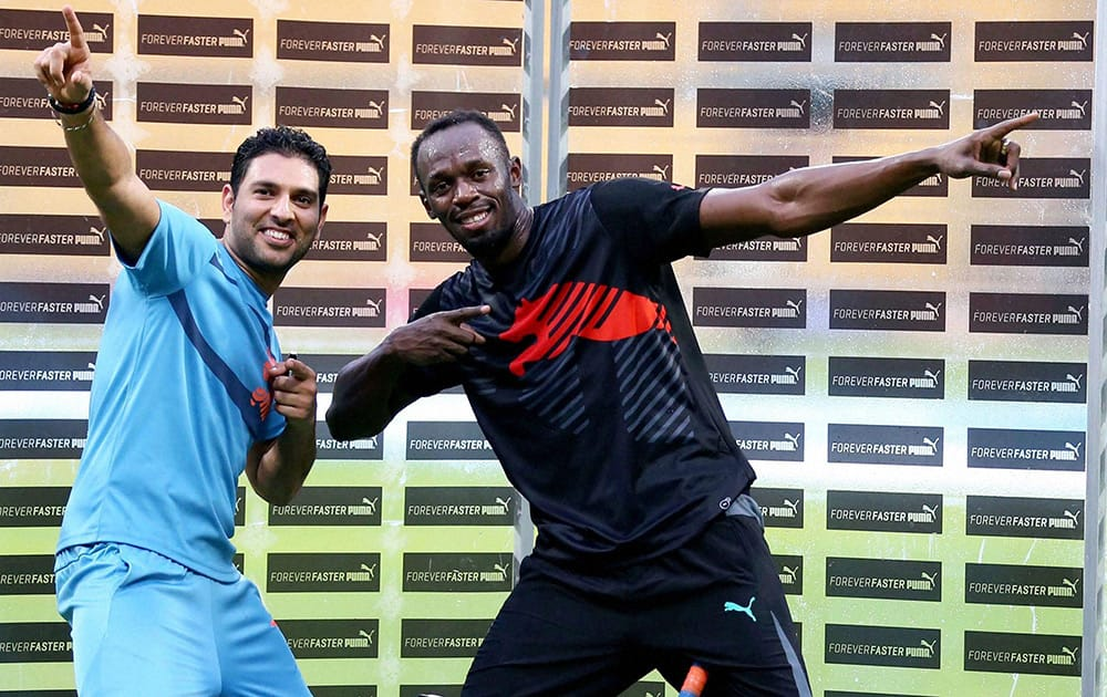 Olympic Gold Medalist sprinter Usain Bolt strikes his trademark pose with cricketer Yuvraj Singh during a friendly cricket match in Bengaluru.