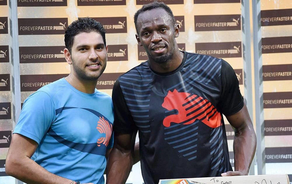 Yuvraj Singh presents a bat signed by him to Olympic Gold Medalist sprinter Usain Bolt in the sidelines of a friendly cricket match in Bengaluru.