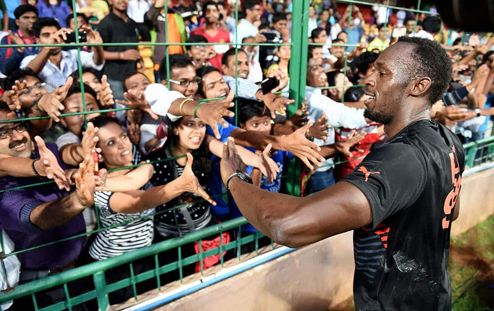 Olympic Gold Medalist sprinter Usain Bolt greets fans during a friendly cricket match in Bengaluru.