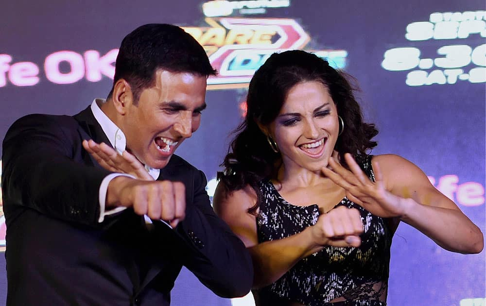 Bollywood actors Akshay Kumar with a French participant of a TV show during a promotional event in New Delhi.
