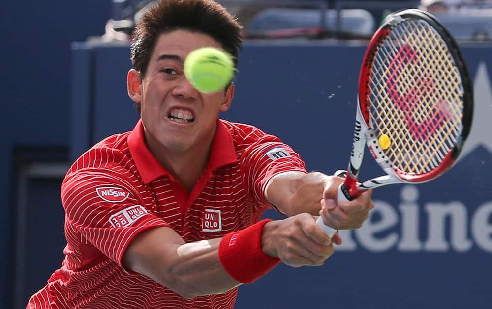 Kei Nishikori, of Japan, returns a shot against Stan Wawrinka, of Switzerland, during the quarterfinals of the 2014 US Open tennis tournament.