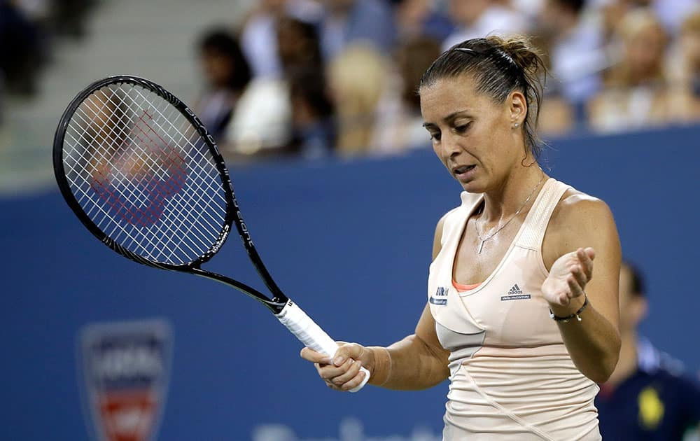 Flavia Pennetta, of Italy, reacts after missing a shot against Serena Williams, of the United States, during the quarterfinals of the US Open tennis tournament.