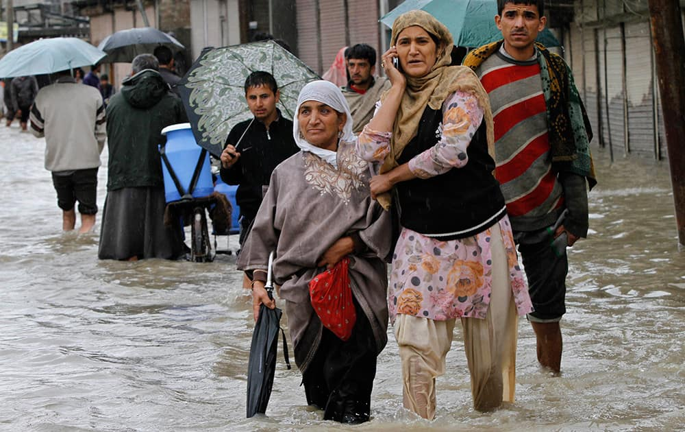A Kashmiri woman speaks on the phone as she wades through floodwaters with others in Srinagar.