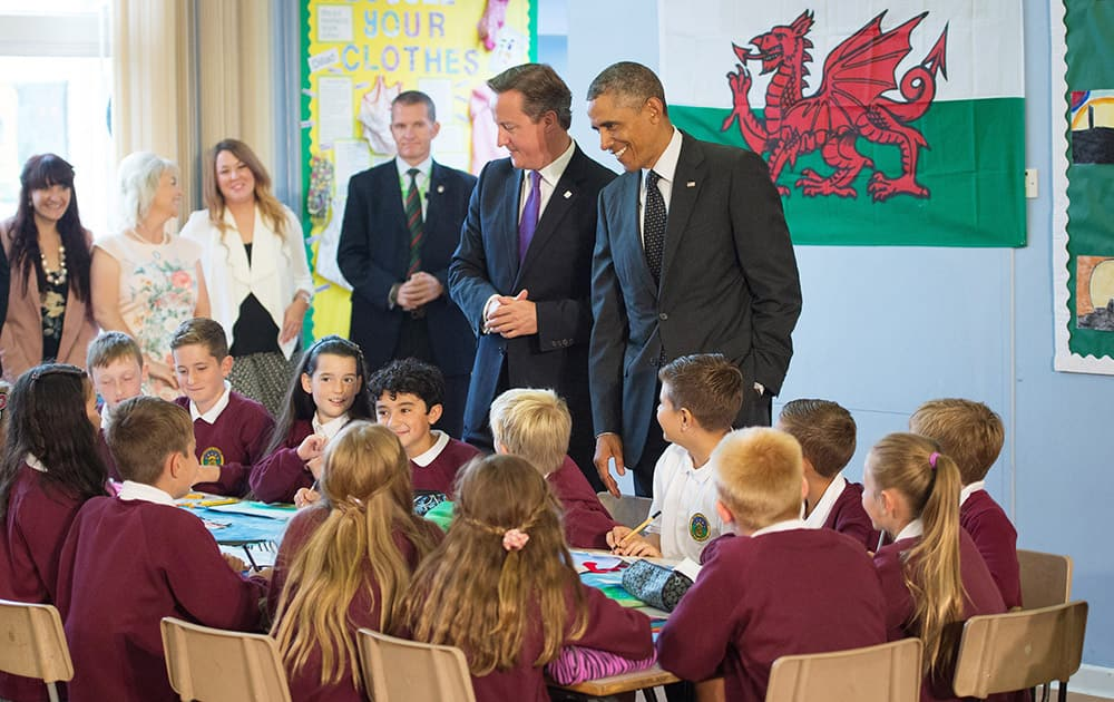 US President Barack Obama, right, and British Prime Minister David Cameron meet children at Mount Pleasant Primary School in Newport, Wales.