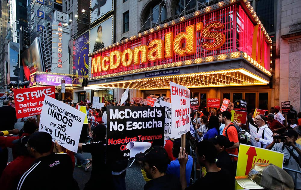 Protesters picket in front of a McDonald's restaurant on 42nd Street in New York's Times Square as police officers move in to begin making arrests.