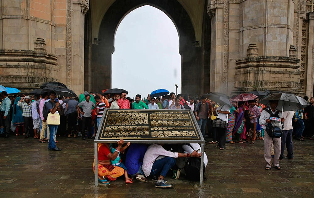Tourists take shelter beneath a plaque that has a description of the Gateway of India monument as it rains in Mumbai.