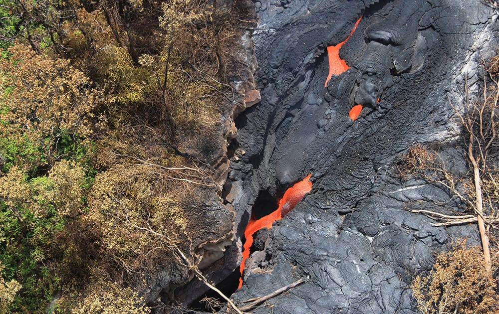 This photo released by the US Geological Survey, fluid lava streams from the June 27 lava flow from the Kilauea volcano in Pahoa, Hawaii.