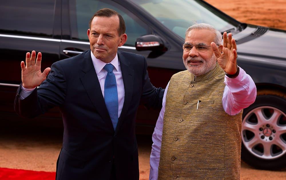 Australian Prime Minister Tony Abbott and his Indian counterpart Narendra Modi wave to photographers in New Delhi.