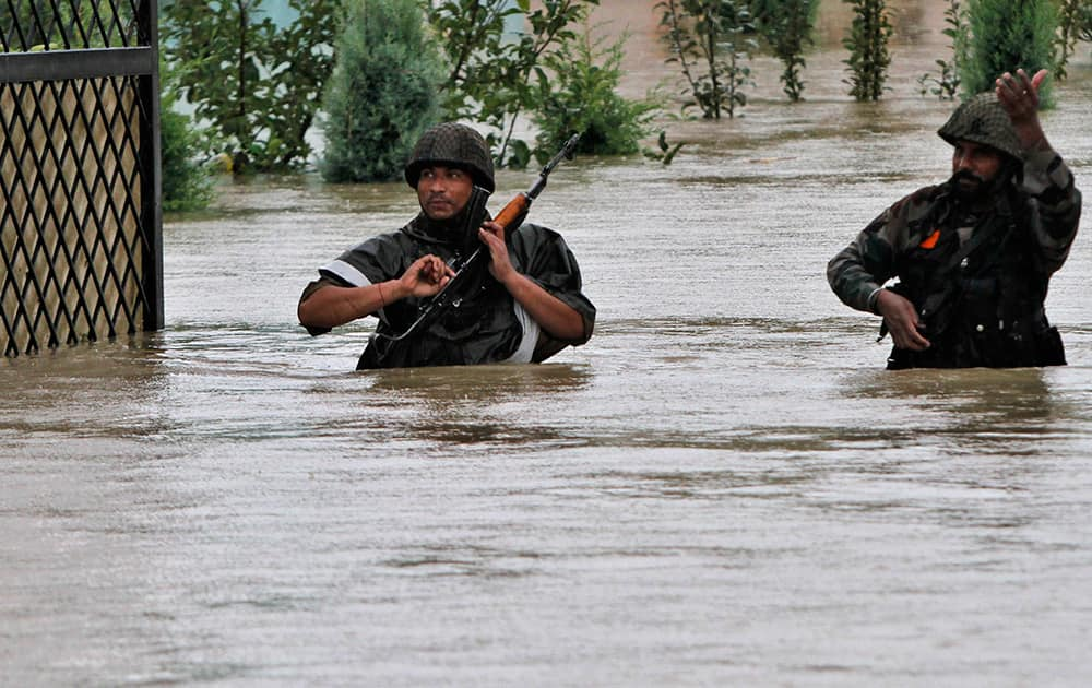 Indian army soldiers walk through a flooded road during a rescue operation in Srinagar.