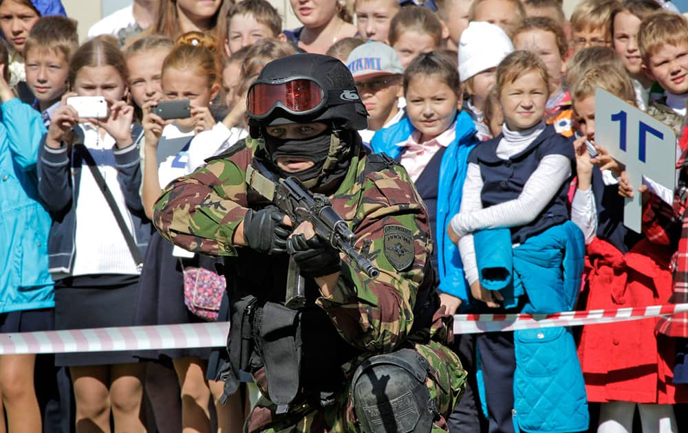 Russian riot police force (OMON) officers demonstrate their skills to schoolchildren during antiterrorist exercises in a school in St. Petersburg, Russia.