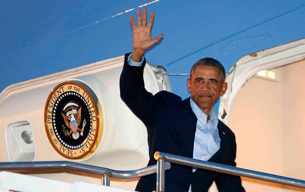 President Barack Obama waves as he boards Air Force One at Royal Air Force Station Fairford, in Gloucestershire, for his return to Washington after attending the NATO summit in Wales.