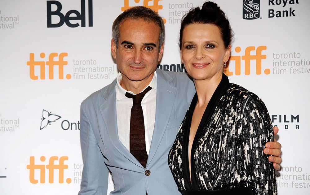 Olivier Assayas, left, writer/director of 'Clouds of Sils Maria,' poses with cast member Juliette Binoche at the premiere of the film at the 2014 Toronto International Film Festival at Princess of Wales Theatre.