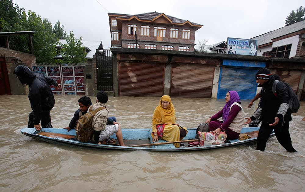 Residents leave a flooded neighborhood on a boat in Srinagar.