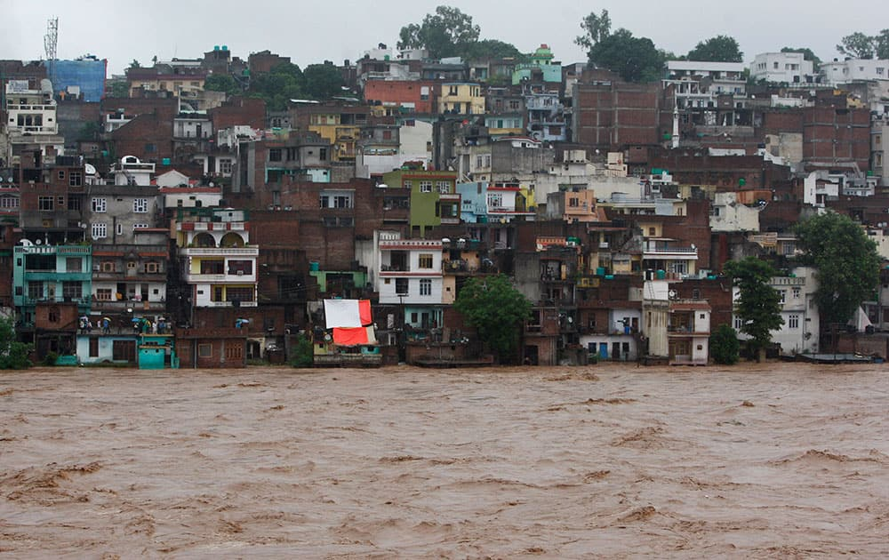 People watch the swelling River Tawi from the roof of their houses in Jammu.