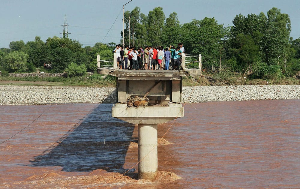 View of a washed away portion of a bridge by floodwater at Phalian Mandal in Jammu.