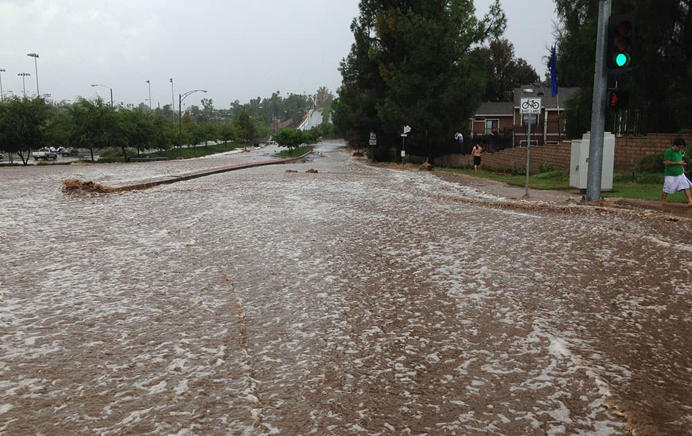 Storm water flows down Chicago Avenue in Riverside, Calif.