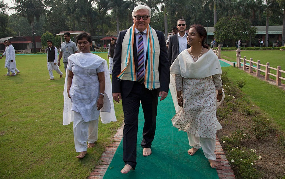 German Foreign Minister Frank-Walter Steinmeier, center, walks after paying tribute at the spot where Mahatama Gandhi was assassinated in New Delhi.