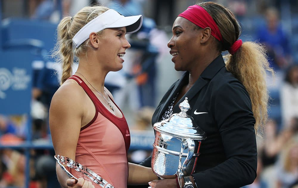 Caroline Wozniacki, of Denmark, left, talks with Serena Williams, of the United States, after Williams won the championship match of the 2014 US Open tennis tournament.