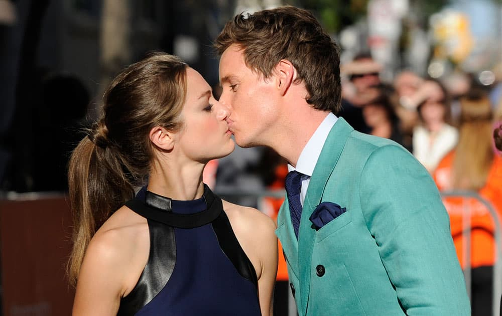 Eddie Redmayne, right, kisses Hannah Bagshawe as they arrive at the premiere for `The Theory of Everything` on day 4 of the Toronto International Film Festival at the TIFF Bell Lightbox.