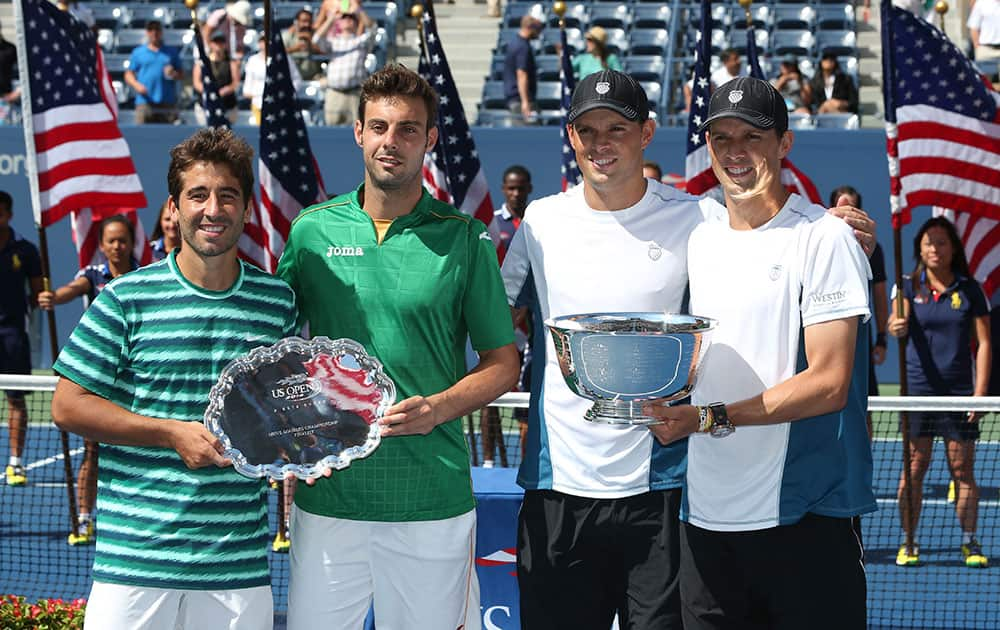 Marc Lopez, left, and Marcel Granollers, of Spain, second from left, pose with Bob, second from right, and Mike Bryan after the Bryan's won the men's doubles championship match of the 2014 US Open tennis tournament.