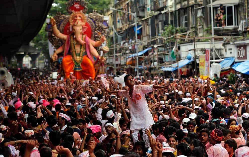 Devotees carry a boy on the shoulder of one of them and dance as a large statue of the Hindu god Ganesh is taken in a procession for immersion in the Arabian Sea on the final day of the festival of Ganesh Chaturthi in Mumbai.