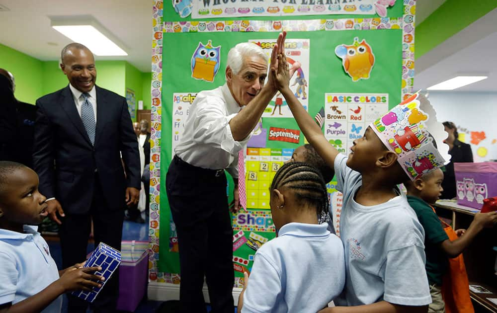 Former Florida Republican Gov. Charlie Crist, right, greets school children as Mass. Gov. Deval Patrick, left, stands near during a campaign event at Mimi's Learning Center, in Pembroke Park, Fla.