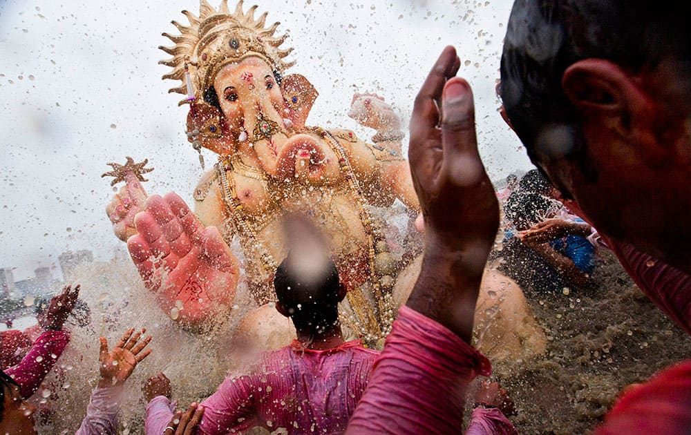 Indian Hindu devotees splash water on a large statue of the elephant-headed Hindu God Ganesha before immersing it in the Arabian Sea on the final day of the festival of Ganesha Chaturthi in Mumbai.