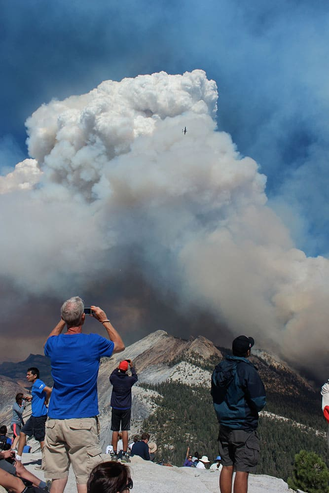 hikers take photos of smoke from a fire rising above Little Yosemite Valley near Yosemite National Park, Calif. About 100 Yosemite National Park visitors were evacuated from the top of Half Dome by helicopter Sunday when a wildfire that started weeks ago in the park's backcountry grew unexpectedly to at least 700 acres, officials said.