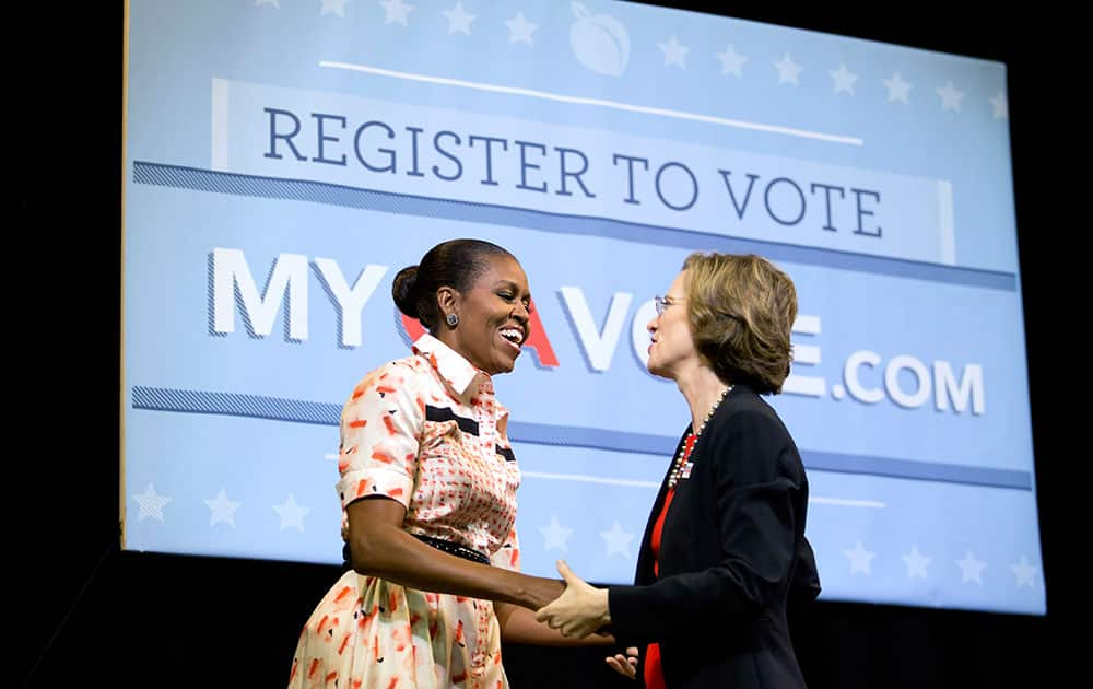 First lady Michelle Obama, left, is greeted by Democratic U.S. Senate candidate Michelle Nunn after being introduced at a voter registration rally, in Atlanta.