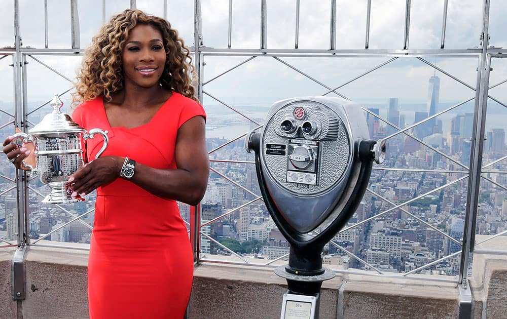 Serena Williams holds the U.S. Open tennis women's singles championship trophy during a visit to the 103rd floor of the Empire State Building, in New York.