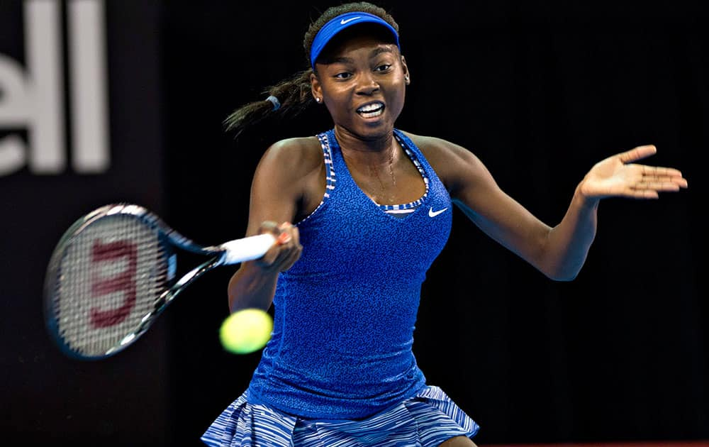 Francoise Abanda, of Canada, returns to Venus Williams, of the United States, during the first round of the Banque Nationale tennis tournament.