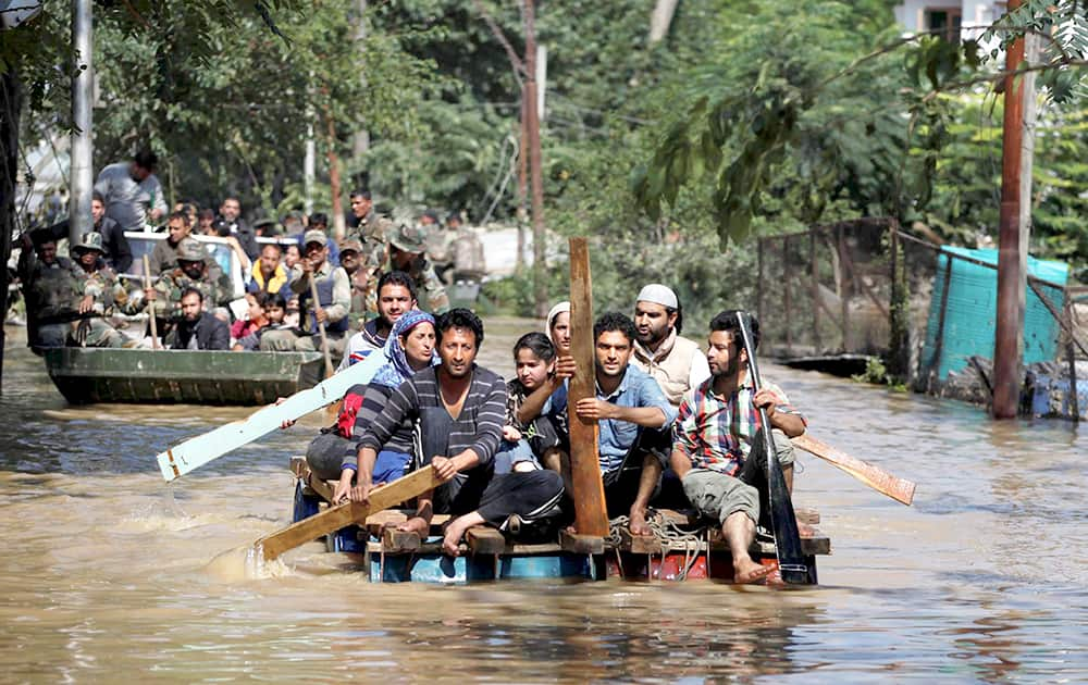 Kashmiri residents use makeshift rafts to rescue flood affected people in Srinagar.