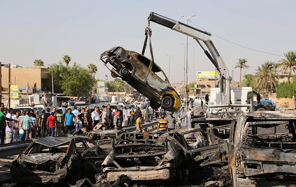 People and security forces gather as a destroyed car is moved from the site of a car bomb explosion in southeastern neighborhood of New Baghdad, Iraq.