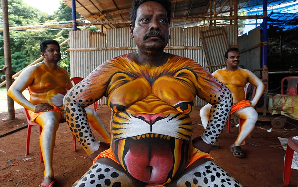 Artists rest after having their bodies painted in the likeness of tigers to perform the annual 'Pulikali' or Tiger Dance in Thrissur, in the southern Indian state of Kerala.
