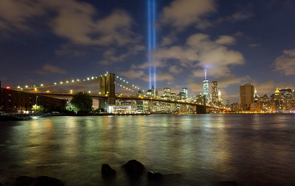 The Tribute in Light rises behind the Brooklyn Bridge and buildings adjacent to the World Trade Center complex, in New York. The tribute, an art installation of 88 searchlights aiming skyward in two columns, is a remembrance of the Sept. 11, 2001, attacks.