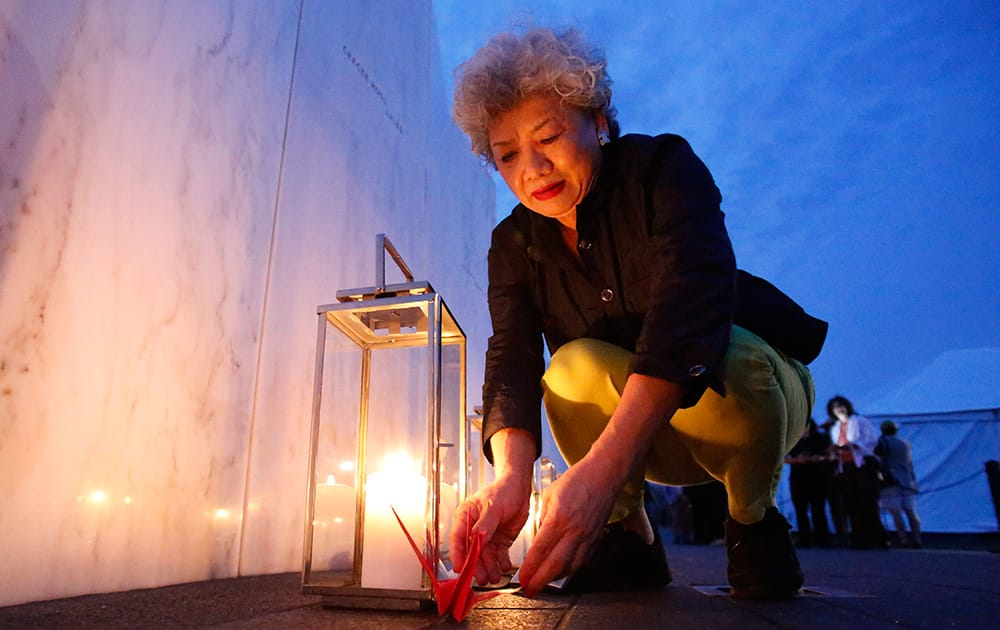 Yachiyo Kuge, the mother of Toshiya Kuge who was a passenger on Flight 93, places origami birds near his name, at the Wall of Names at the Flight 93 National Memorial in Shanksville, Pa.. Thursday marks the 13th anniversary of the Sept. 11 terror attacks.