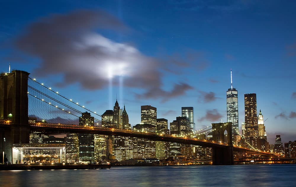 THE TRIBUTE IN LIGHT RISES BEHIND THE BROOKLYN BRIDGE AND BUILDINGS ADJACENT TO THE WORLD TRADE CENTER COMPLEX, IN NEW YORK.