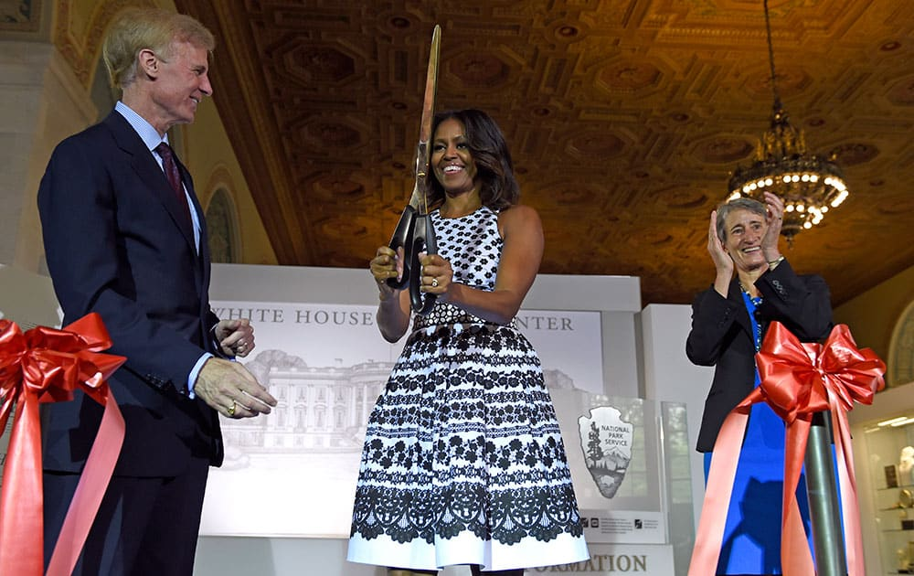 First lady Michelle Obama flanked by White House Historical Association chairman and incoming Washington Post Publisher Fred Ryan, left, and Interior Secretary Sally Jewell, holds up a large pair of scissors after cutting the ribbon during an opening ceremony for the newly renovated White House Visitors Center in Washington.