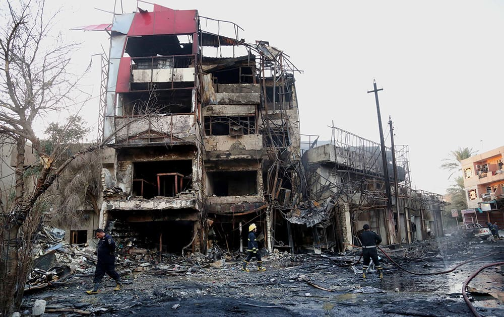 Firefighters inspect the aftermath of a double car bomb attack which took place at a busy market in Ghadeer district in southeastern Baghdad, Iraq.