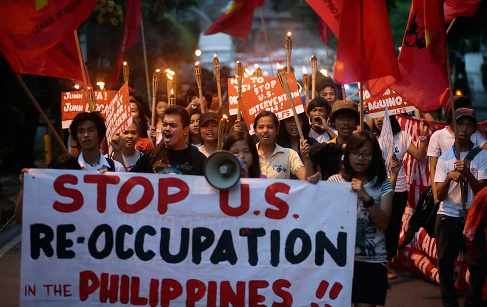 Members of the League of Filipino Students, LFS, shout slogans as they march for a 'Torch Protest' towards the US Embassy to mark 37 years of their anti-US stance, in Manila, Philippines.