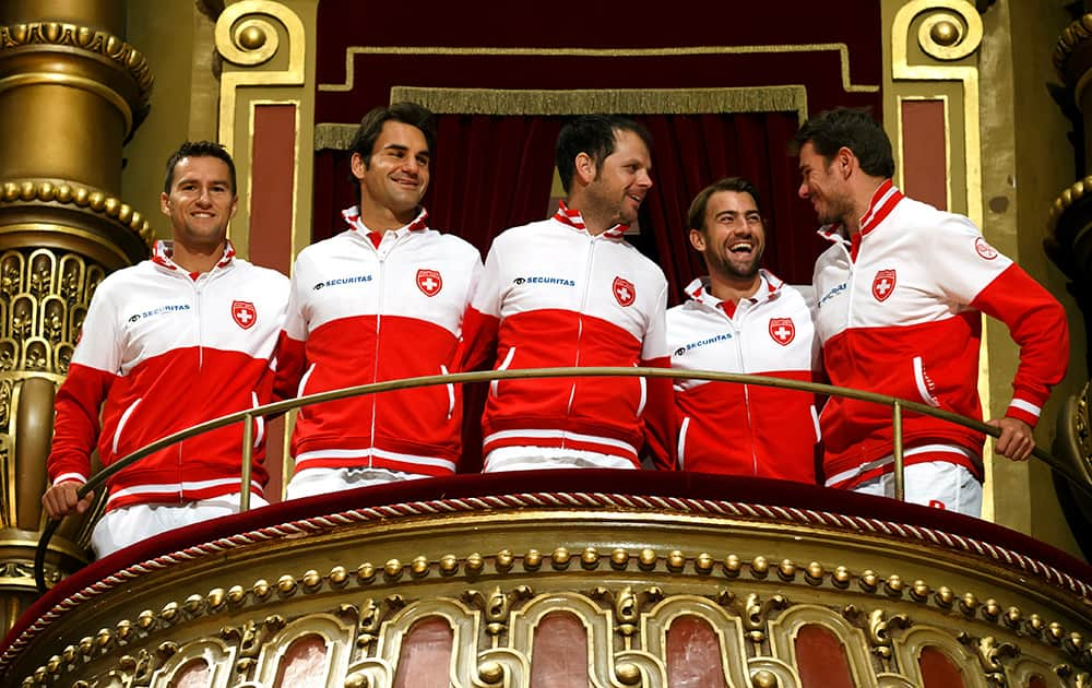 Swiss Davis Cup Team: Marco Chiudinelli, Roger Federer, Swiss Davis Cup Team captain Severin Luethi, Michael Lammer, and Stanislas Wawrinka, from left to right, pose for the photographers on the balcony at the Victaoria Hall, after the drawing of the tennis Davis Cup World Group Semifinal matches between Switzerland and Italy, in Geneva, Switzerland.