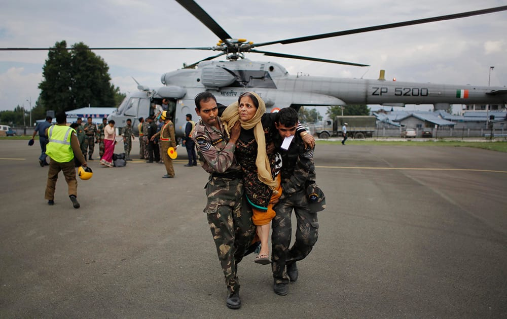 Indian soldiers carry a rescued flood victim at the Air Force Station in Srinagar.