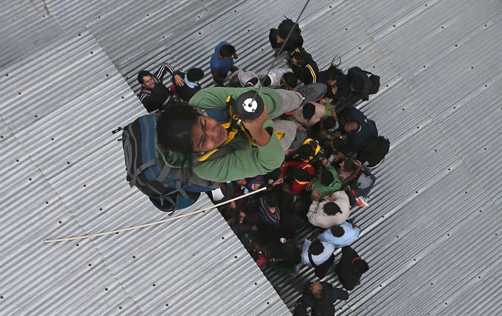 A tourist is airlifted from the roof of a of a five-story hotel, four of which are submerged in floodwaters, in Srinagar.
