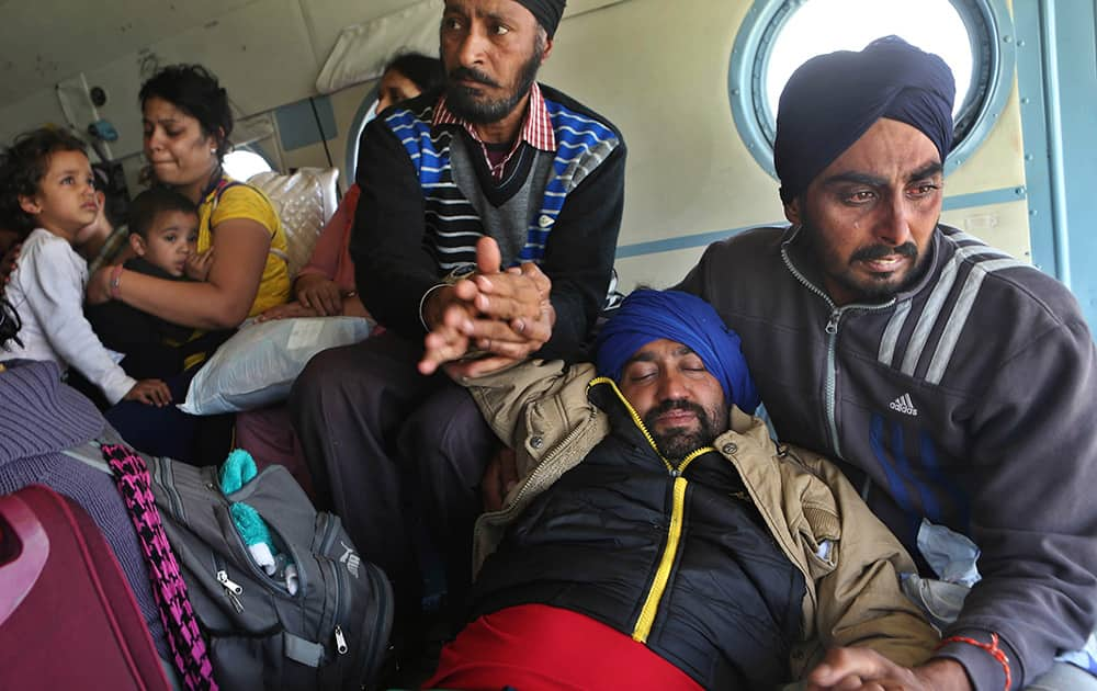 Tears roll down the cheeks of a relative of a seriously ill tourist as they hold him inside an Indian air force helicopter after being rescued from a flooded neighborhood in Srinagar.