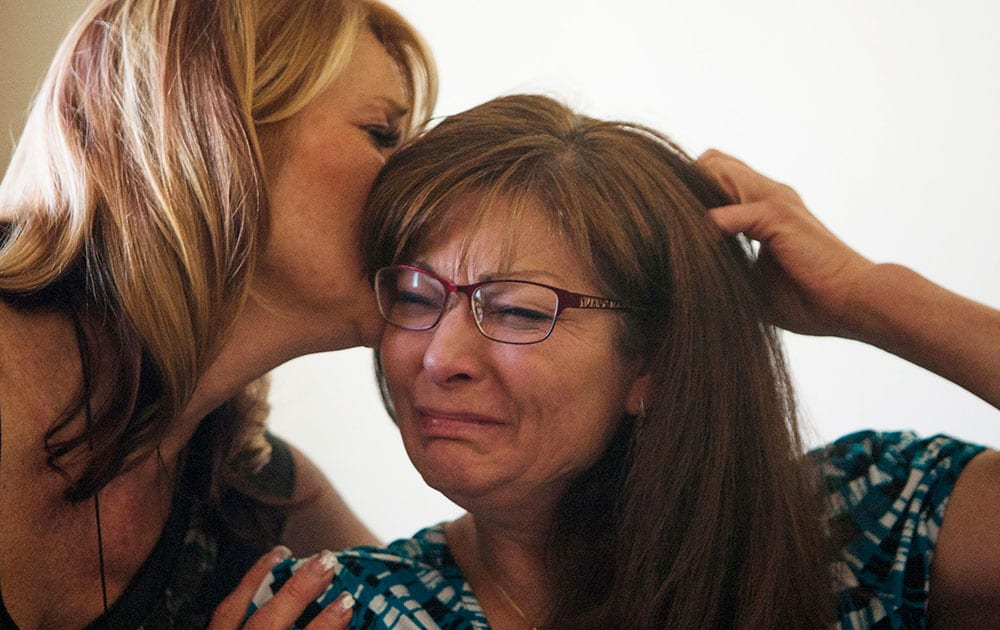 Susan Hunt, right, is consoled by her sister, Cindy Moss, as she speaks about her son, Darrien Hunt, who was killed by police Wednesday, at her home in Saratoga Springs, Utah.